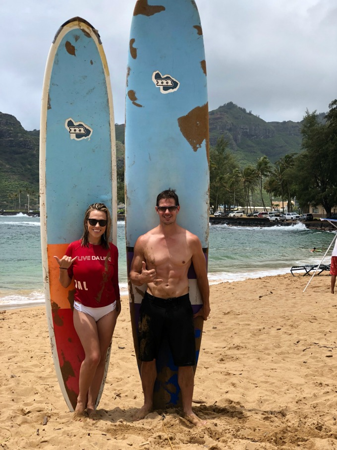 Jessica and Kyle standing by surfboards