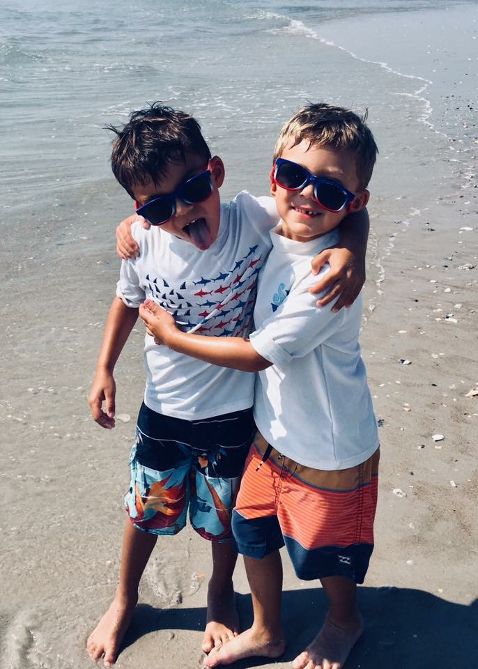 Twin brothers playing at the beach.