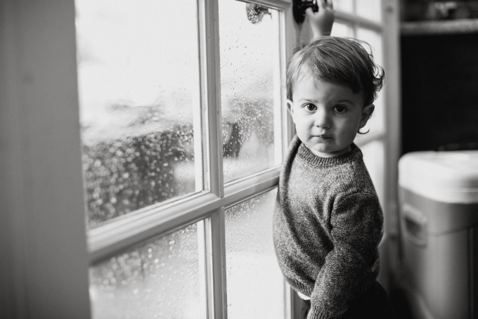 young boy standing by a window in black and white