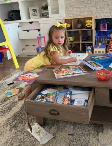 girl coloring pictures in playroom