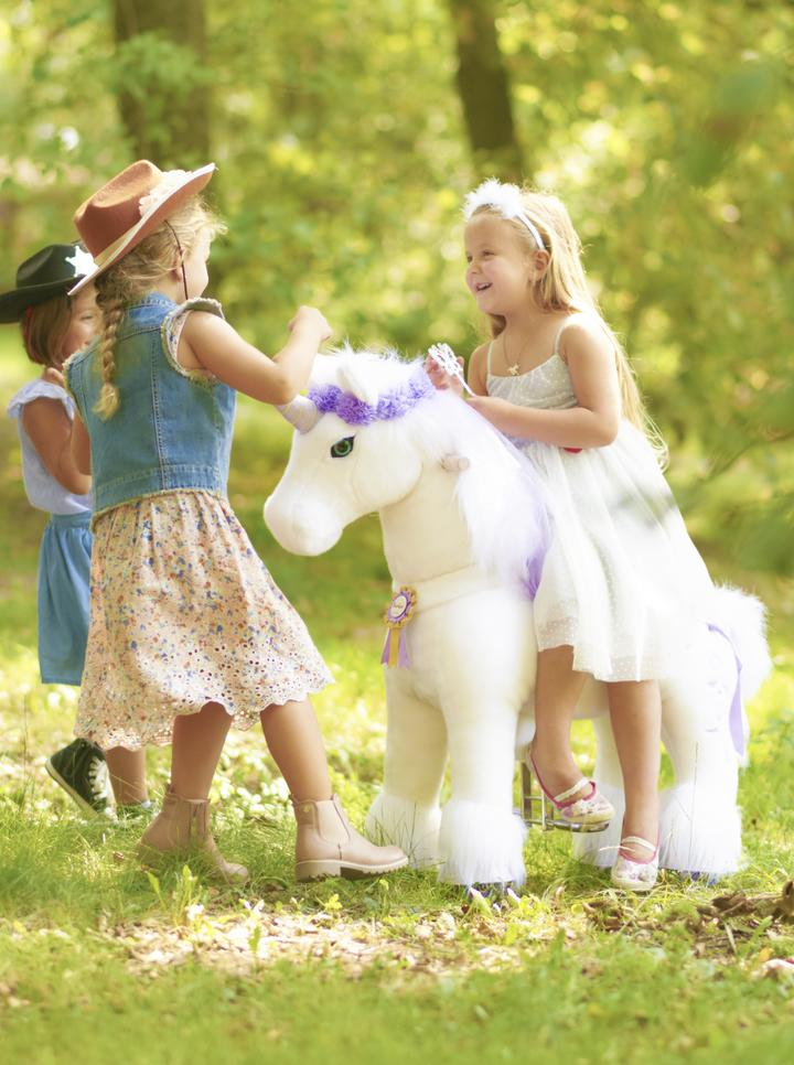 girls playing with unicorn ponycycle