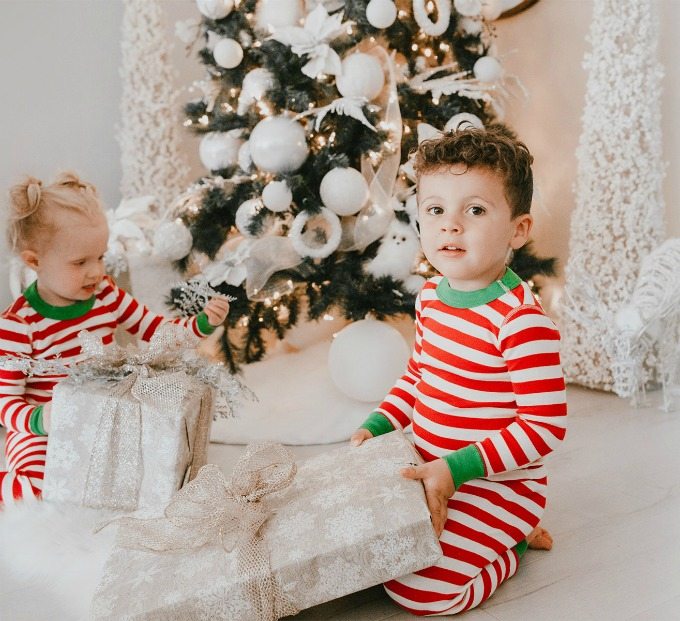 kids holding presents by christmas tree