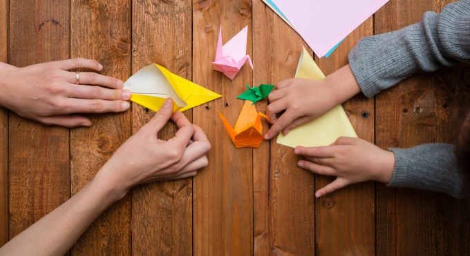 hands making origami shapes
