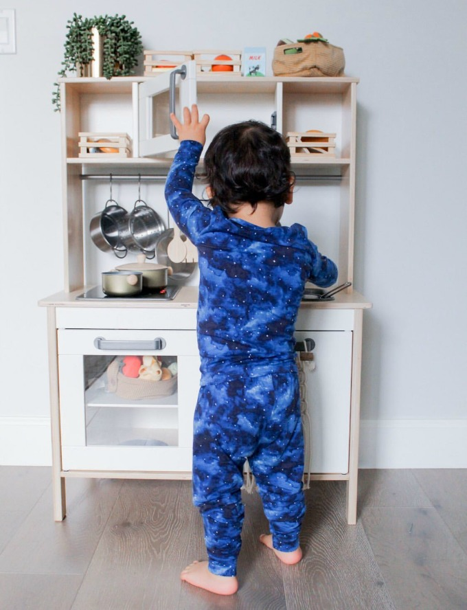 Kid with Lovey&Grink pajamas playing with kitchen