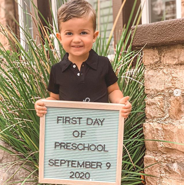 boy holding sign for first day of preschool