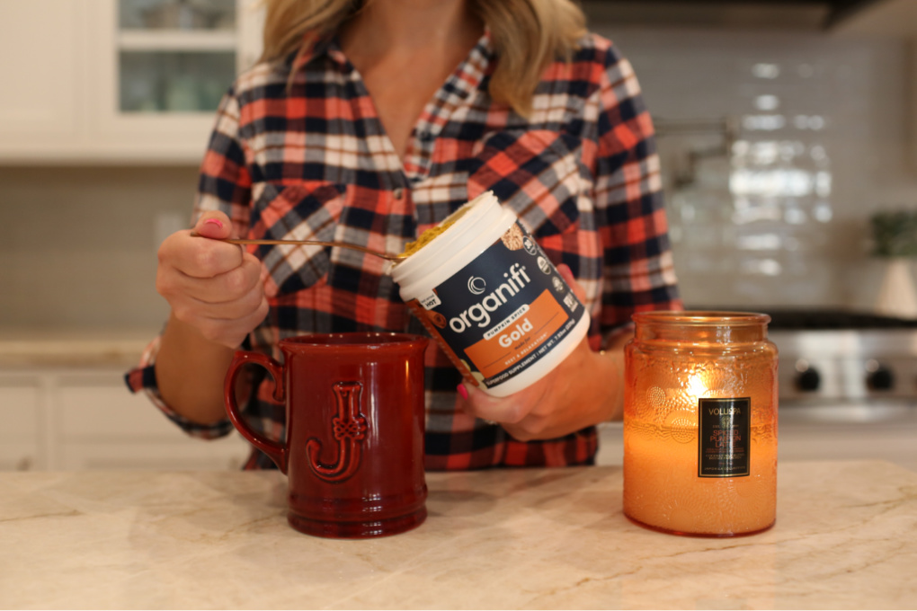 woman with pumpkin spice drink and candle