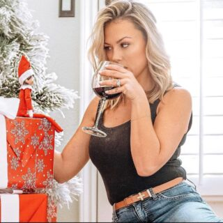 Jessica Hall drinking wine and looking at Elf on the Shelf