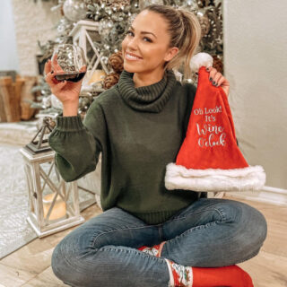 "Jessica Hall holding wine glass and Santa hat with words ""It's wine o'clock"" on embroidered on the hat"
