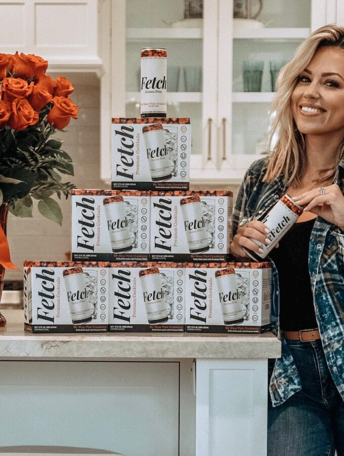 Jessica Hall standing in her kitchen with boxes of Fetch canned cocktails on her counter next to her.
