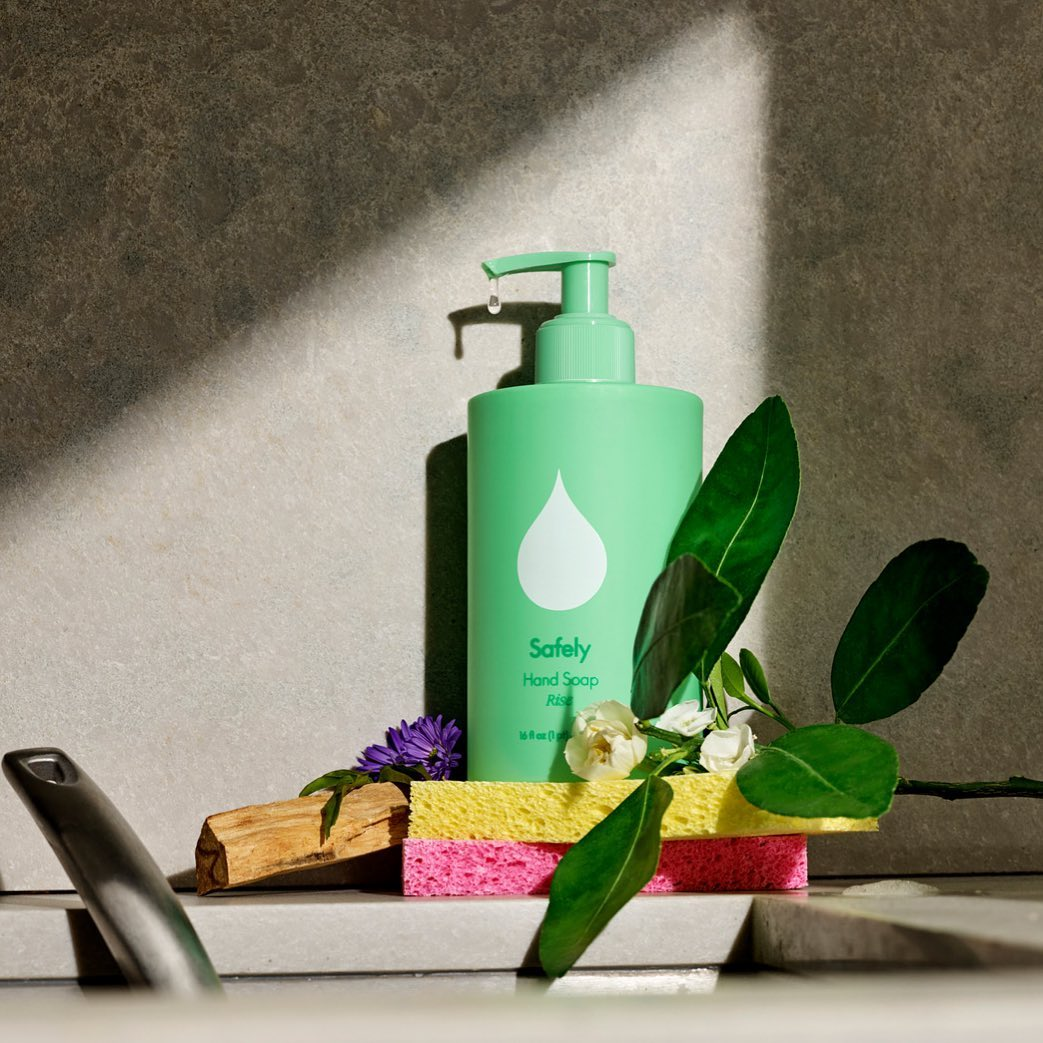 Bottle of green Safely hand soap sitting behind sponges and green leaves by a sink.