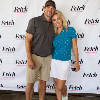 Jessica Hall and husband, Kyle, wearing golf clothes and standing in front of a step and repeat with Fetch Cocktail logos.