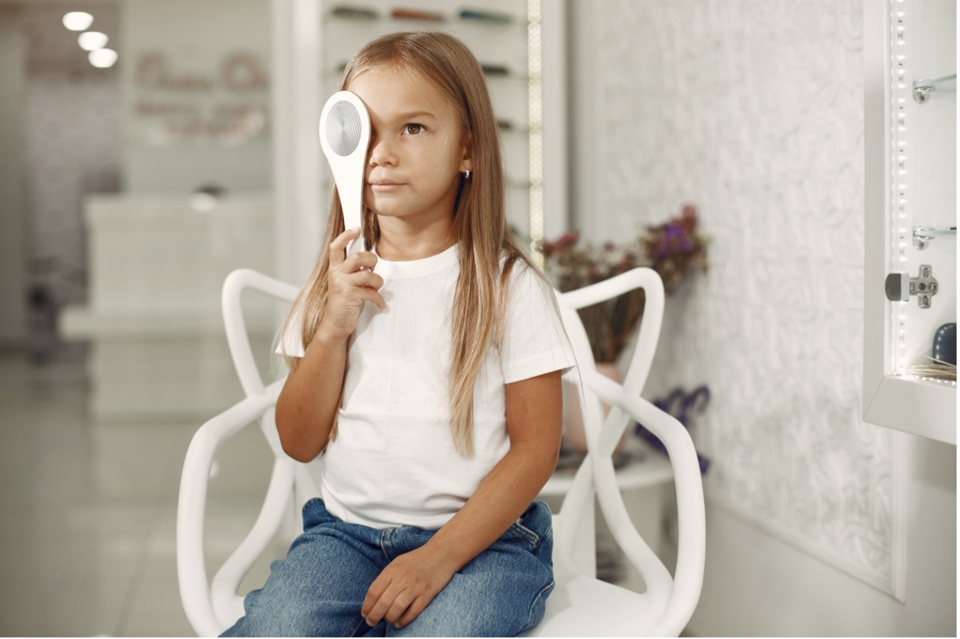 Girl istting in white chair holding an eye tester over one eye.