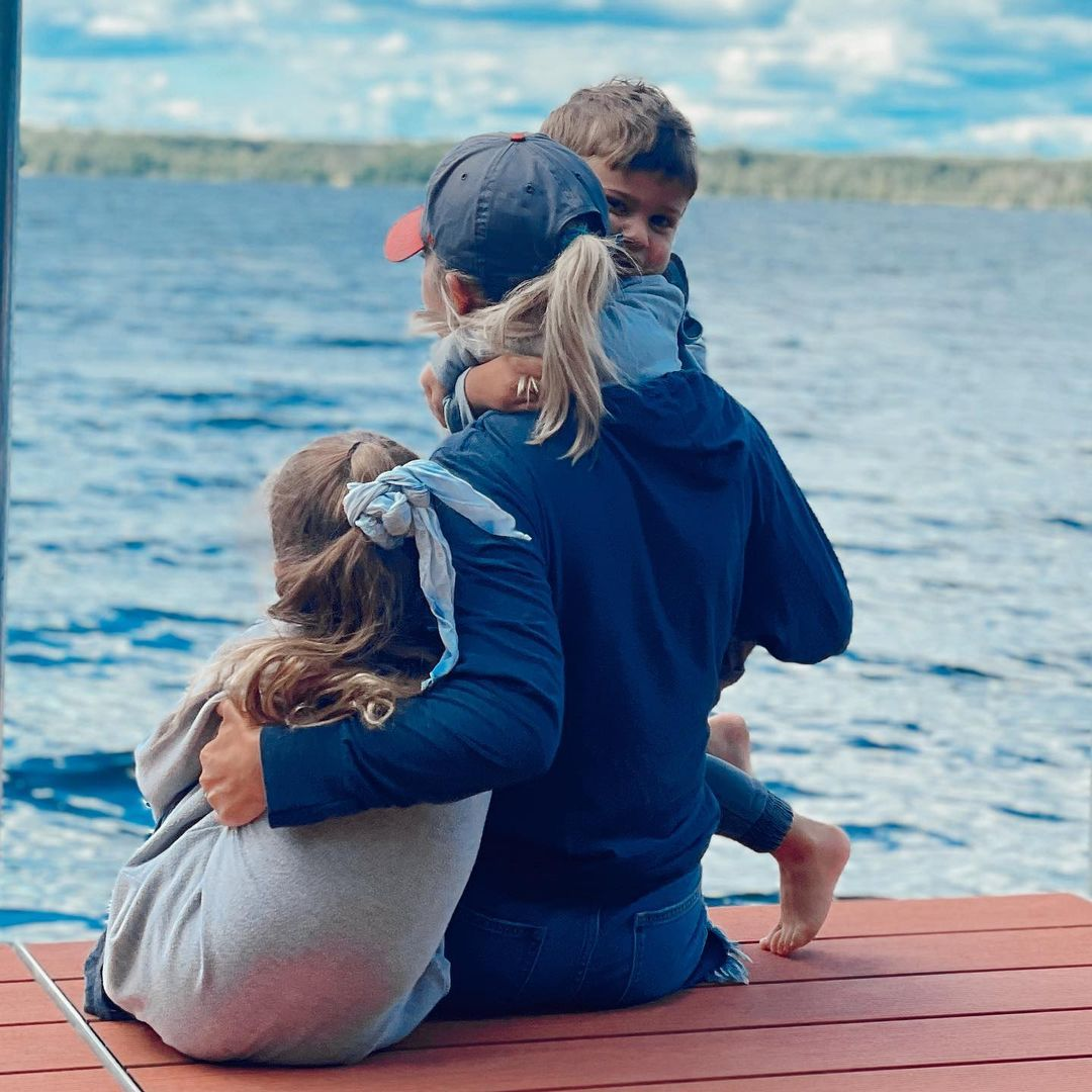 Jessica Hall and kids sitting on a dock looking out at a lake.
