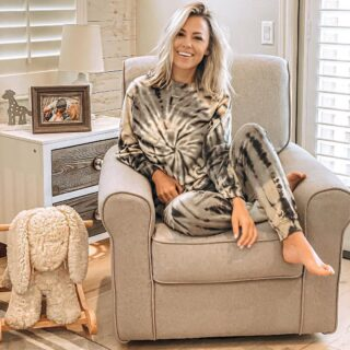 Jessica Hall sitting on a beige chair in a child's room wearing black and white tie-dyed sweats.