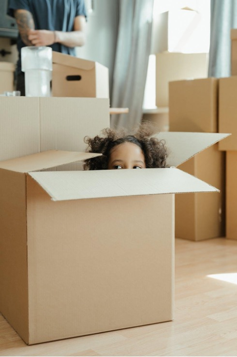 Boxes stacked in living room with a kid peeking out of one.