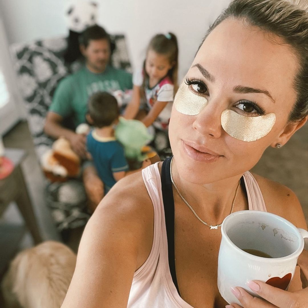 Jessica Hall holding a coffee cup and wearing gold under-eye strips with her family blurred in the background.