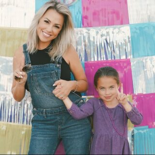 Jessica Hall and her daughter, Sophie, standing in front of a multicolor wall.