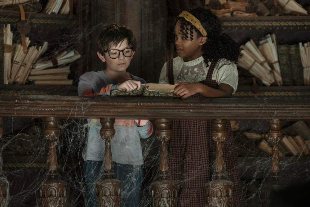 Winslow Fegley and Lidya Jewett from the movie NIghtbooks standing in a dirty library looking at a book.