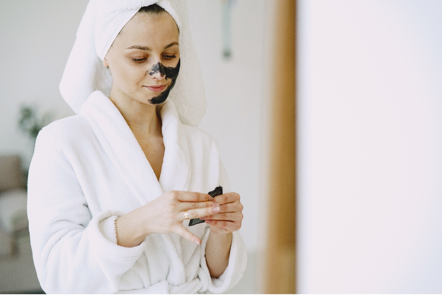 Woman applying face mask wearing a bathrobe and towel on her head.