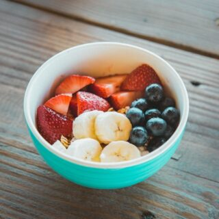 Teal bowl with strawberries, blueberries, and bananas.