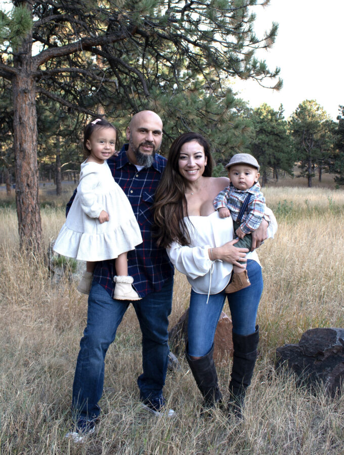 Denise and her family standing in a field in front of a tree.